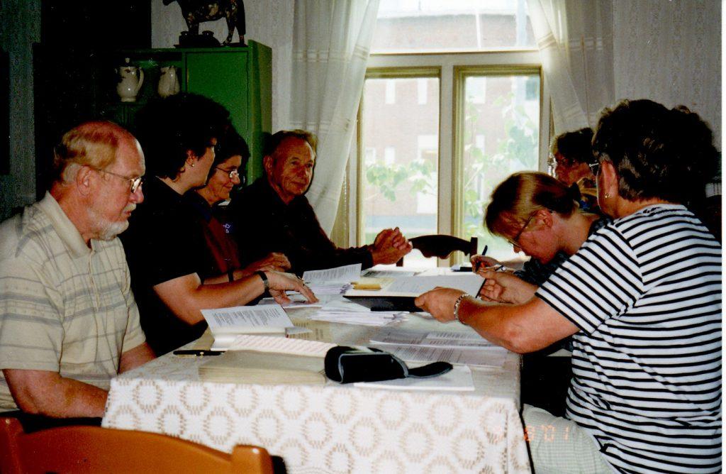 Ihmisiä on kokoontunut pöydän äärelle keskustelemaan